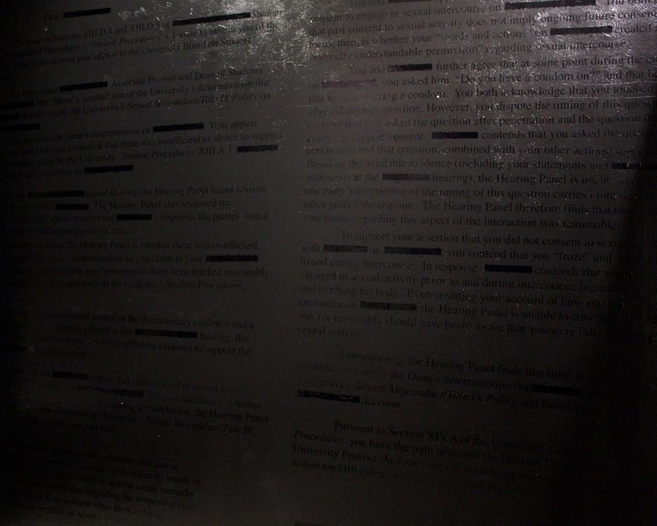 black vinyl transcript of sexual assault administrative letter on black wall