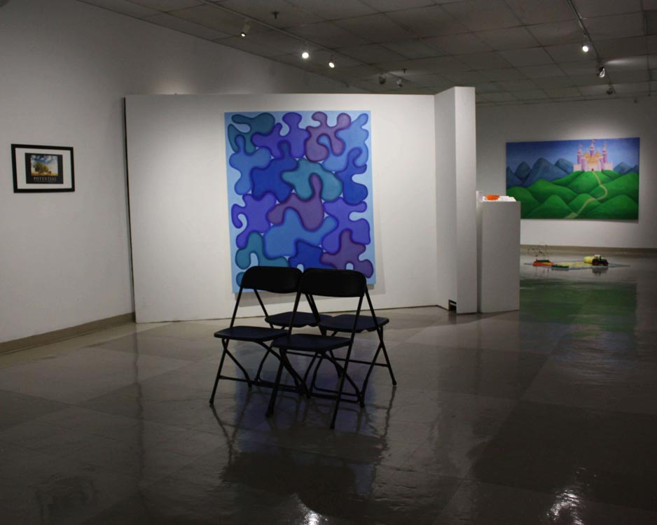 perspective of gallery, foldable chairs are in the center of the room with a blue amorphous painting and smaller posters on the walls