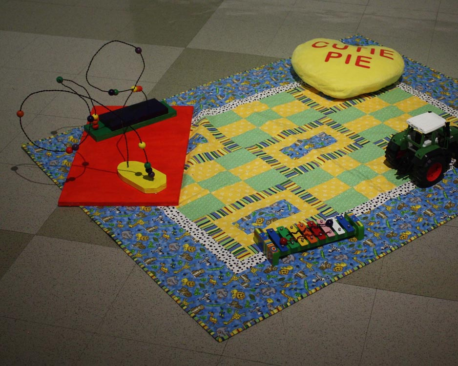 childish blanket with heart shaped pillow, toy truck, xylophone, and wooden bead and wire sculpture